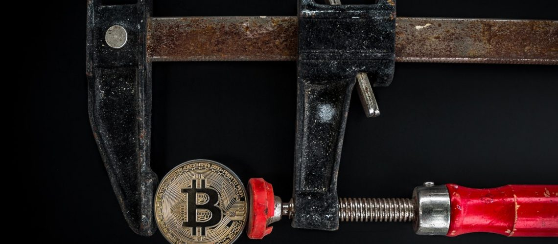 black-and-red-caliper-on-gold-colored-bitcoin-1099339